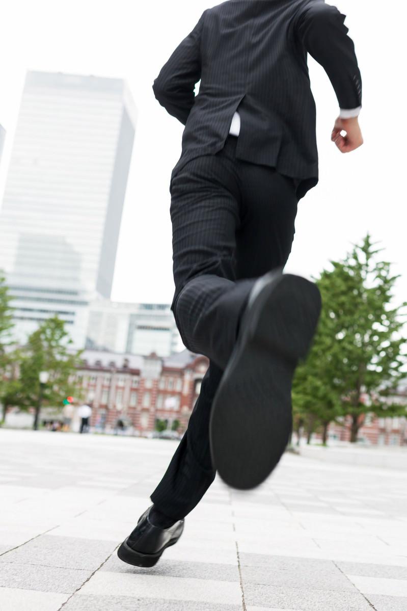 「ダッシュするスーツ姿のビジネスマン」の写真