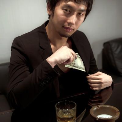 「懐から万札を出す男性」の写真素材