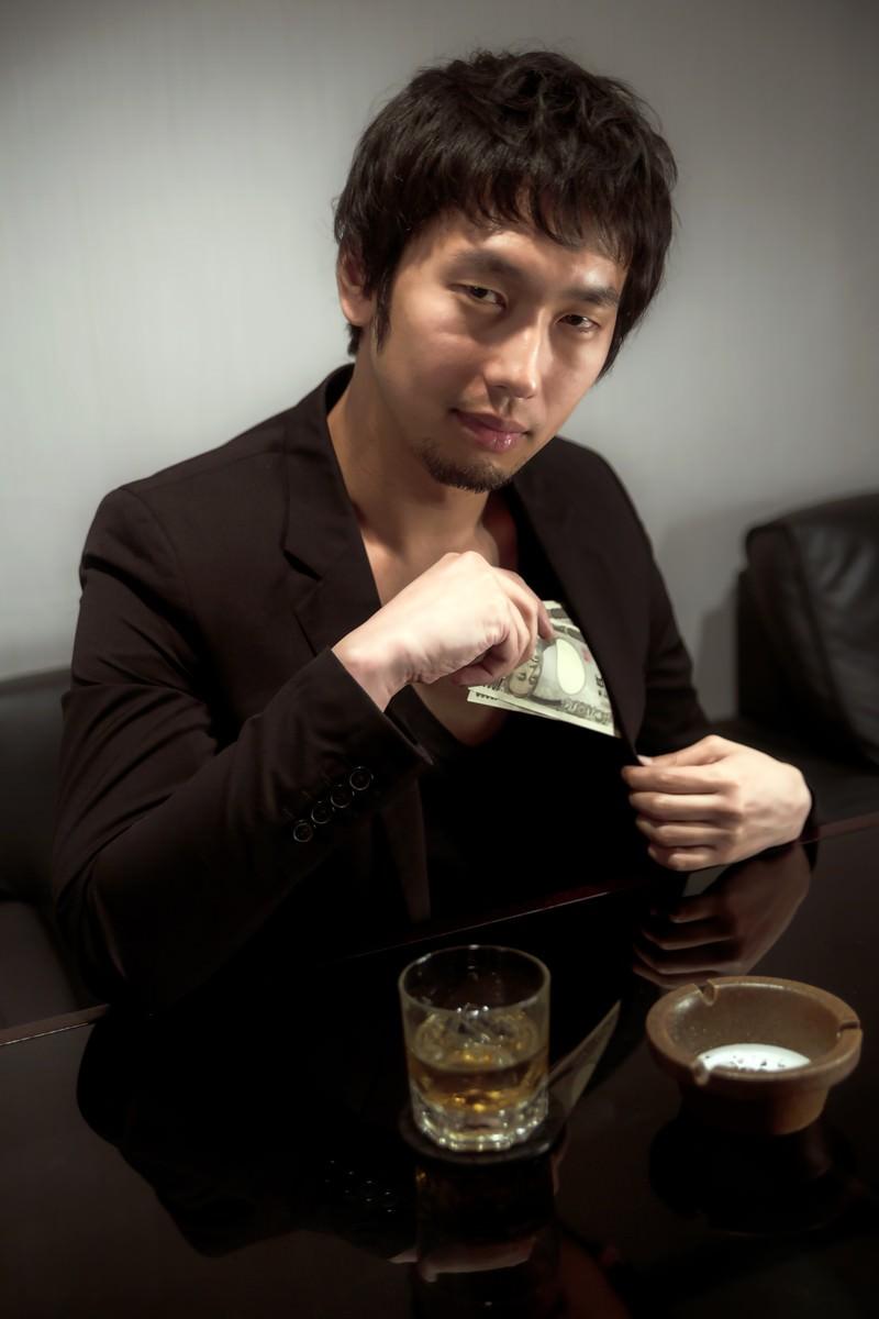 「懐から万札を出す男性」の写真[モデル:大川竜弥]