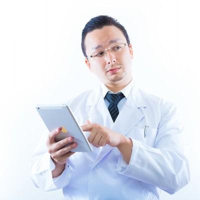 タブレットを持って検索をする白衣のドクターの写真
