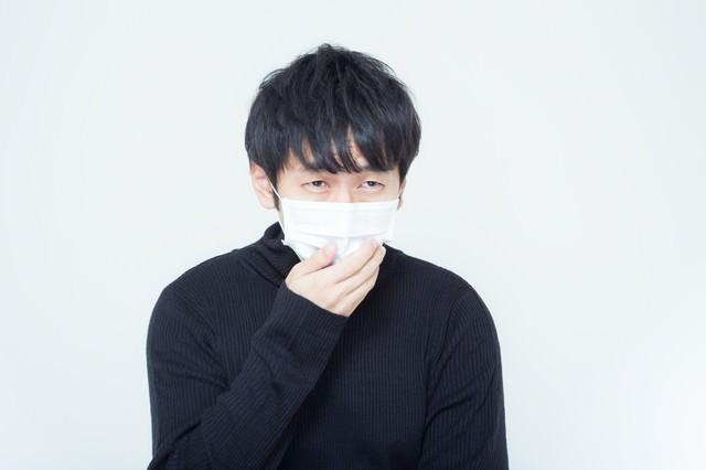 花粉症に悩まされるマスクを付けた男性の写真
