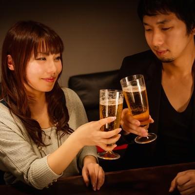 バーで乾杯する男女の写真