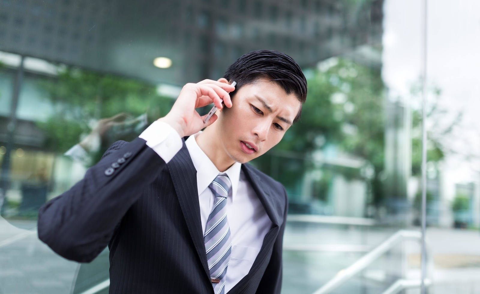 「先方からの連絡にいち早く対応するやり手のビジネスマン先方からの連絡にいち早く対応するやり手のビジネスマン」[モデル:川崎大洋]のフリー写真素材を拡大