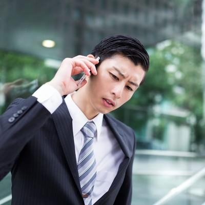 「先方からの連絡にいち早く対応するやり手のビジネスマン」の写真素材