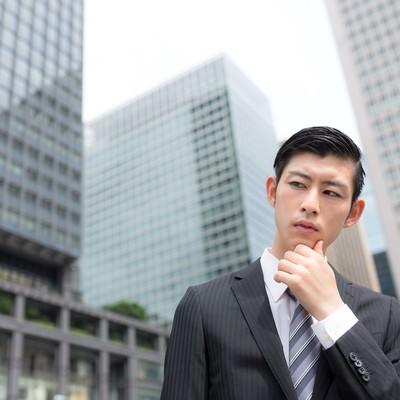 「オフィス街で考えこむビジネスパーソン」の写真素材