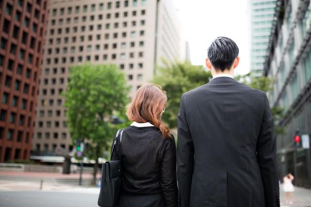 信号待ちをするスーツ姿の男女の写真
