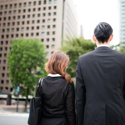 「信号待ちをするスーツ姿の男女」の写真素材