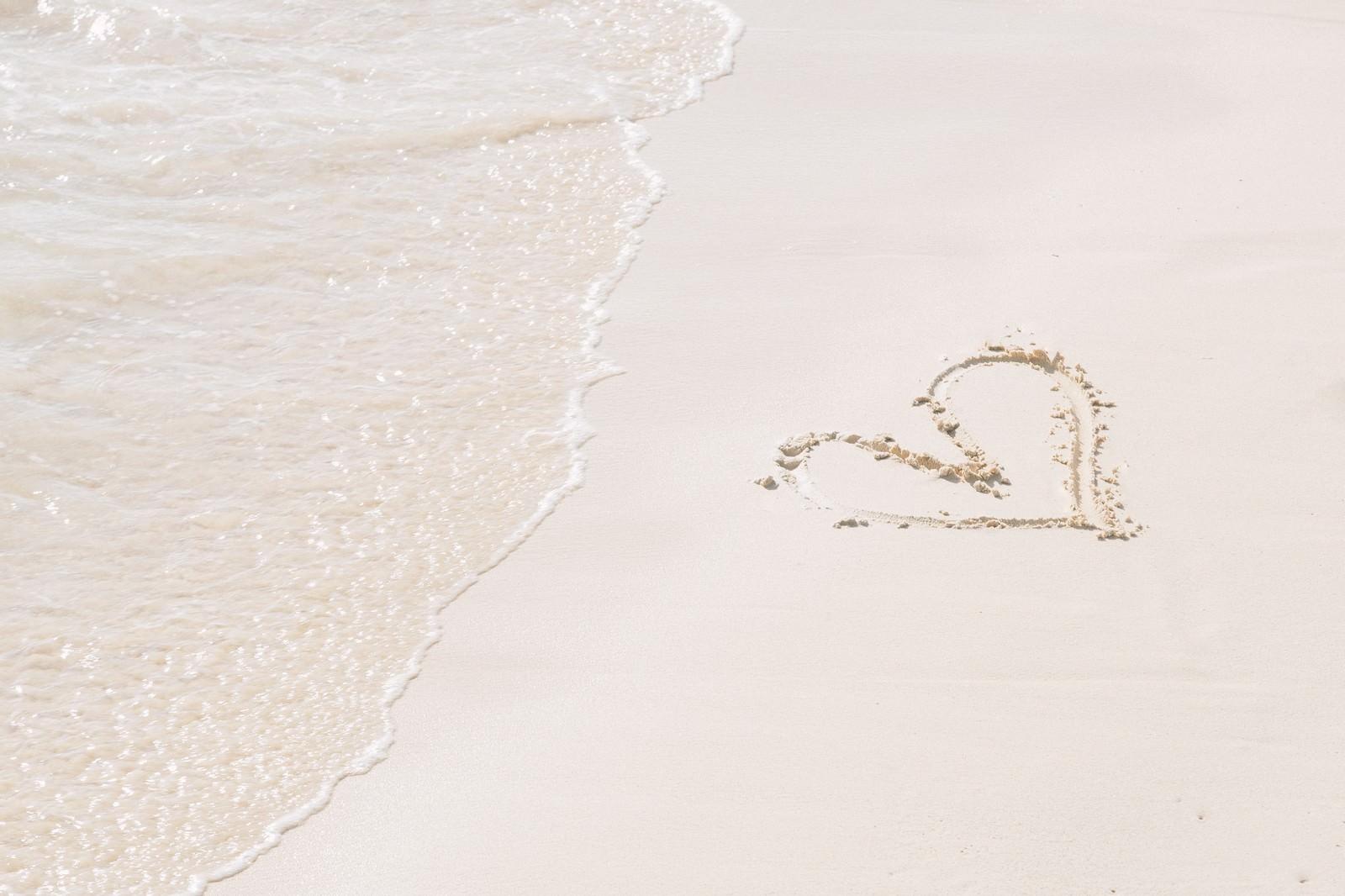 「ハートが描かれた砂浜と波」の写真