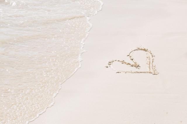ハートが描かれた砂浜と波の写真