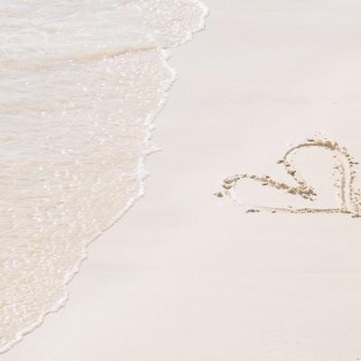 「ハートが描かれた砂浜と波」の写真素材