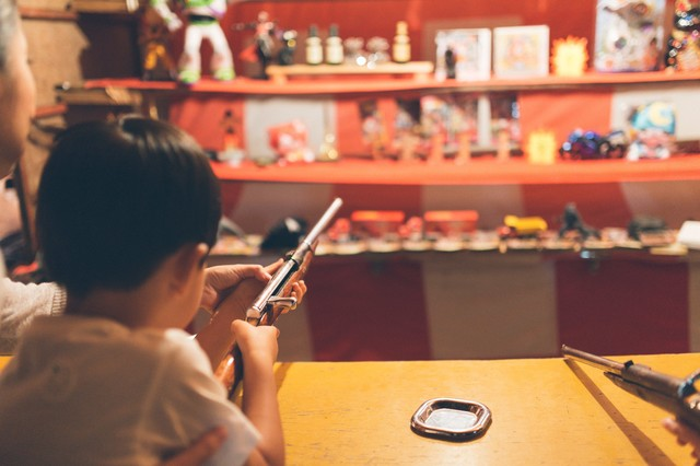 お祭りの出店にある射撃で銃を構える子供の写真