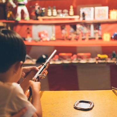 「お祭りの出店にある射撃で銃を構える子供」の写真素材