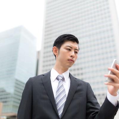 「スマホで株価を確認するエリートビジネスマン」の写真素材