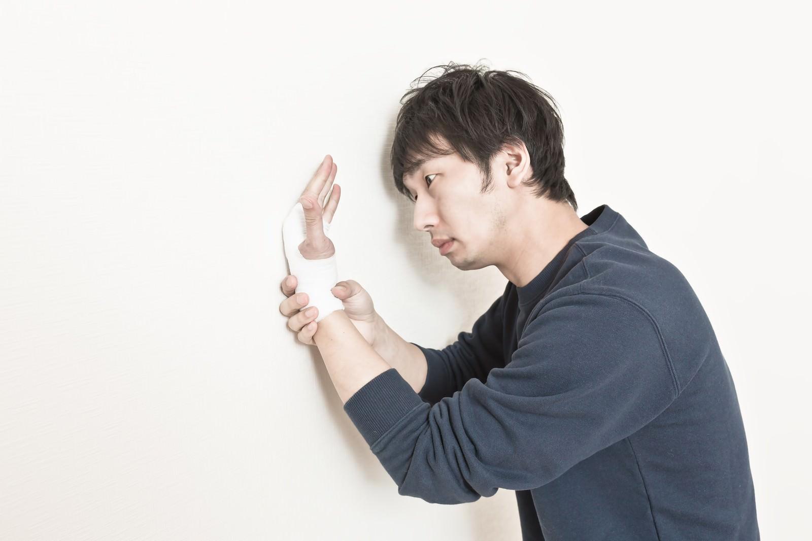 「壁を叩きすぎて手首を痛めてしまったニート」の写真[モデル:大川竜弥]