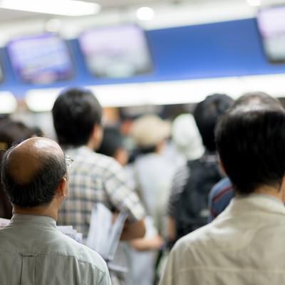 場外馬券場のモニターでレースを確認する人々の写真