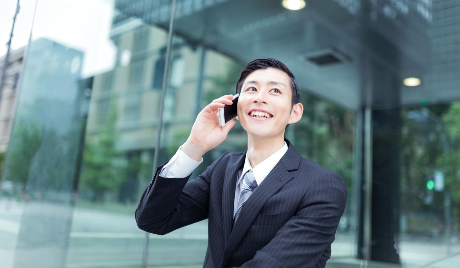 「取引先から受注をもらって笑顔な会社員(スーツ)取引先から受注をもらって笑顔な会社員(スーツ)」[モデル:川崎大洋]のフリー写真素材を拡大