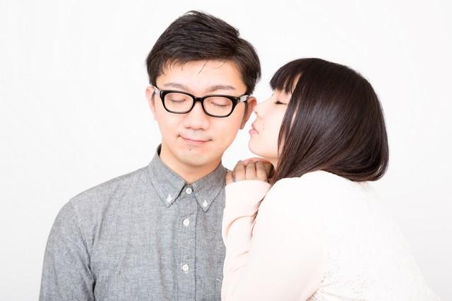 ほっぺたにキスをしようとする彼女と穏やかな表情の彼氏の写真