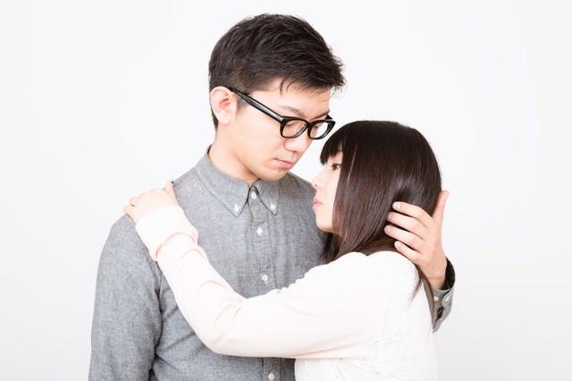 口付けをしようと彼女をやさしく抱擁する彼氏の写真