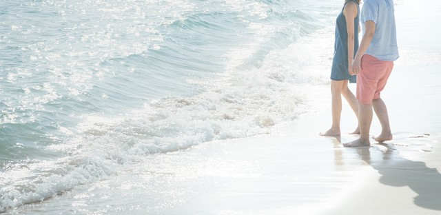 押し寄せる波に引き寄せられるカップルの写真