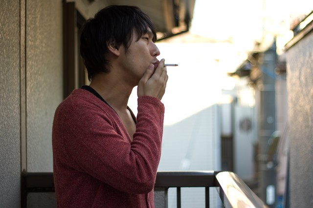 ベランダでしかタバコが吸えないお父さんの写真