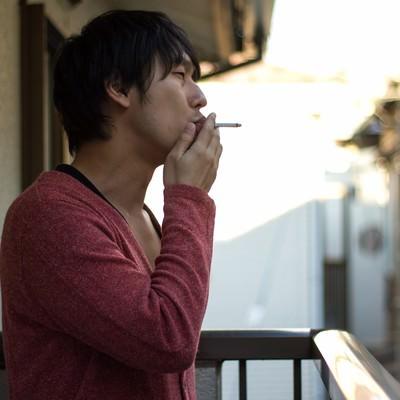 「ベランダでしかタバコが吸えないお父さん」の写真素材