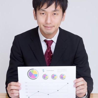 「グラフが書かれた資料を見せて提案するディレクター」の写真素材