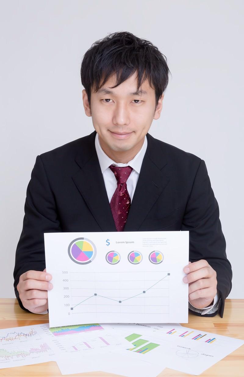 「グラフが書かれた資料を見せて提案するディレクター」の写真[モデル:大川竜弥]
