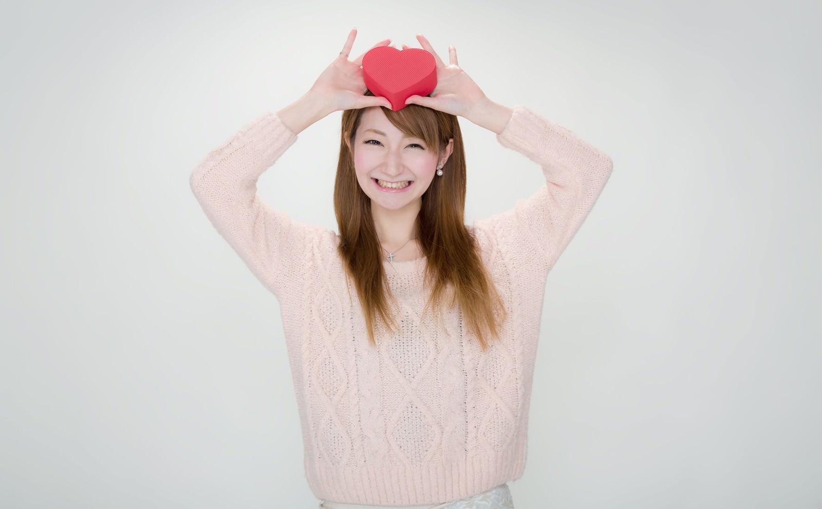 「「じゃじゃーん!」ハート形のプレゼントを見せる女の子」の写真[モデル:to-ko]
