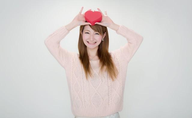「じゃじゃーん!」ハート形のプレゼントを見せる女の子の写真