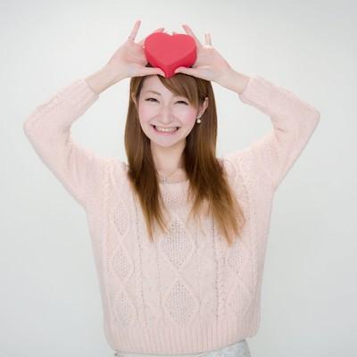 「「じゃじゃーん!」ハート形のプレゼントを見せる女の子」の写真素材