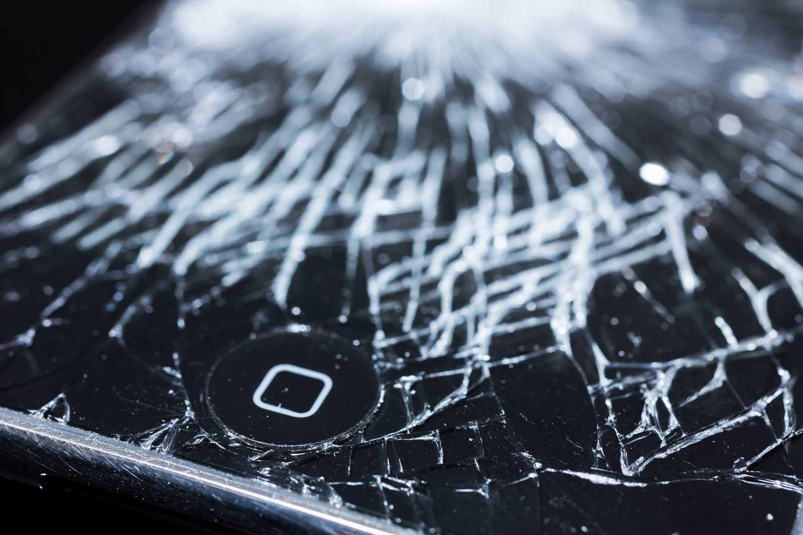 「液晶にヒビが入ったスマホとホームボタン」の写真