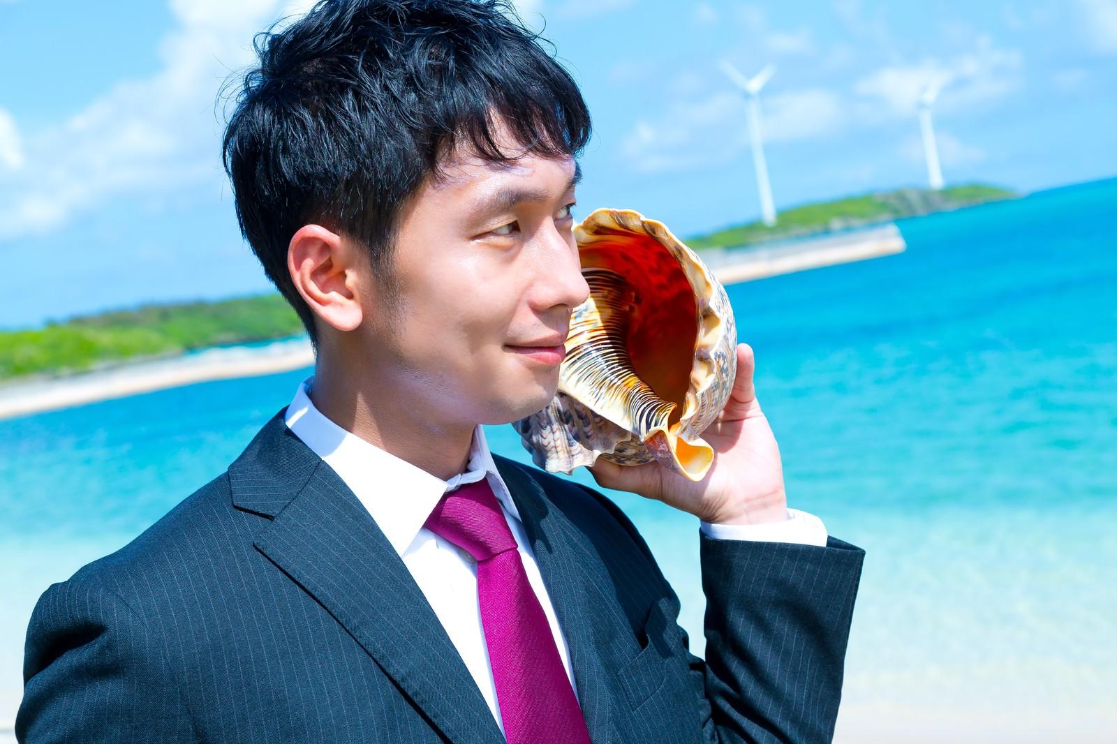 「南の島で貝フォンを使用するビジネスマン」の写真[モデル:大川竜弥]