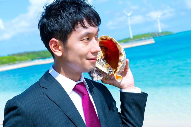 南の島で貝フォンを使用するビジネスマンの写真