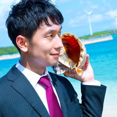 「南の島で貝フォンを使用するビジネスマン」の写真素材
