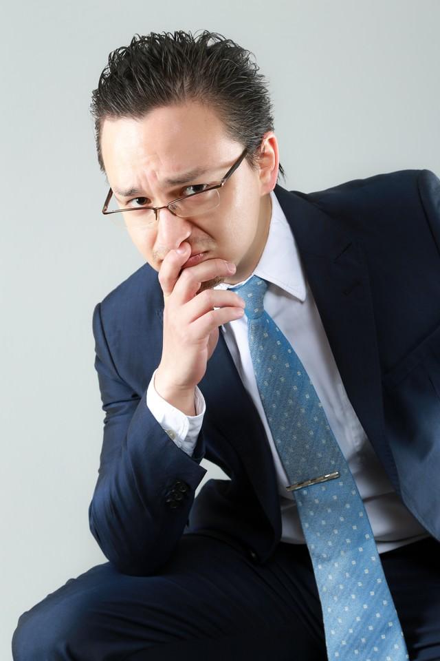 困った顔をする外資系の男性会社員の写真