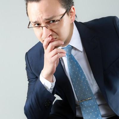 「困った顔をする外資系の男性会社員」の写真素材