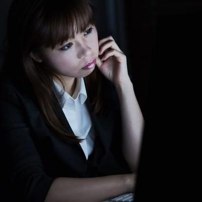 消灯したオフィスの中で残業仕事をするOLの写真