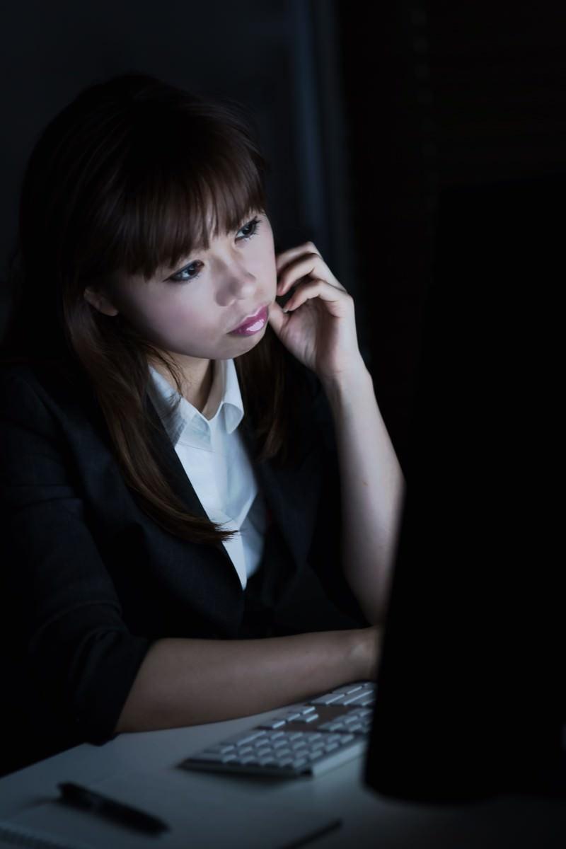 「消灯したオフィスの中で残業仕事をするOL」の写真[モデル:暢子]