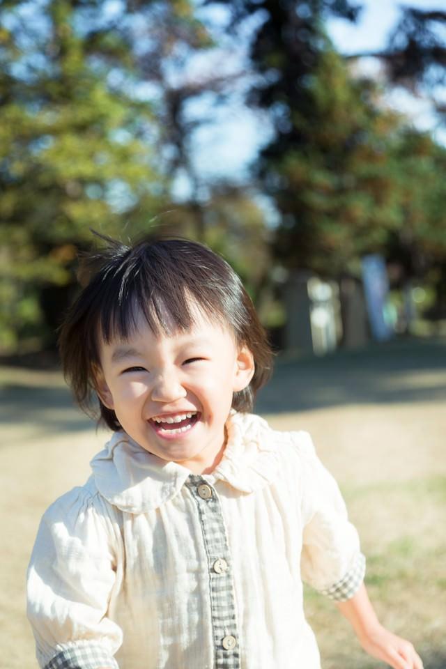 笑顔で公園を走り回る子供の写真