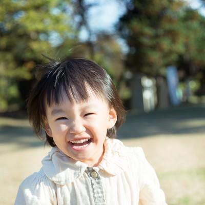 「笑顔で公園を走り回る子供」の写真素材