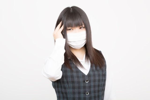花粉症と頭痛で苦しむOLの写真
