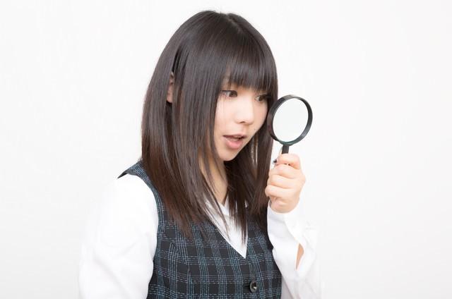 虫眼鏡を覗きこむOLの写真