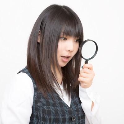 「虫眼鏡を覗きこむOL」の写真素材