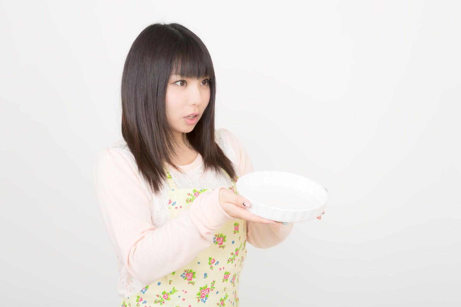 「大きなお皿を両手で持ったエプロン姿の女性」の写真[モデル:Lala]