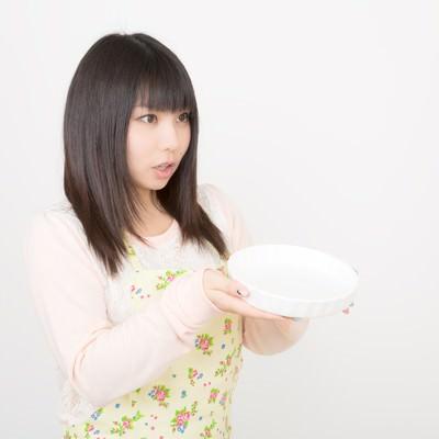 「大きなお皿を両手で持ったエプロン姿の女性」の写真素材