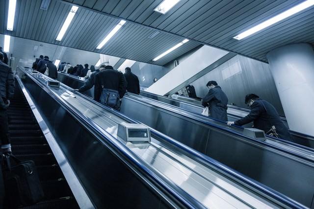 エスカレーターに乗るサラリーマンの写真