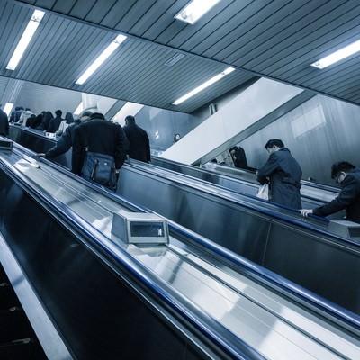 「エスカレーターに乗るサラリーマン」の写真素材