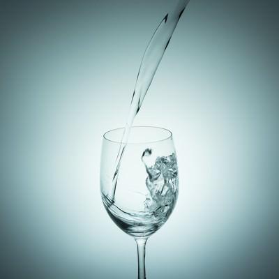「グラスに水を注ぐ瞬間」の写真素材