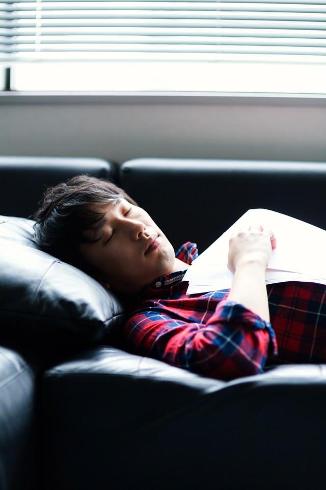 資料を持ちながら寝落ちする男性の写真