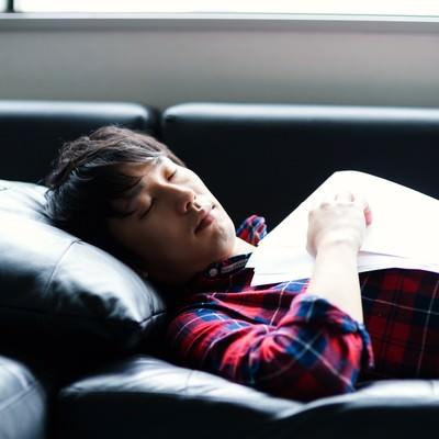 「資料を持ちながら寝落ちする男性」の写真素材